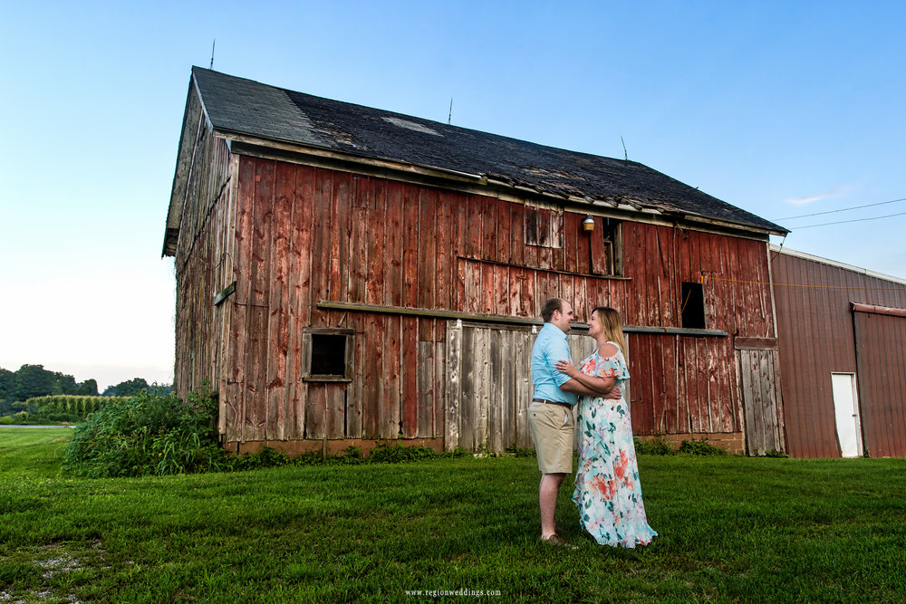 A young couple embraces in front of the Four Corners barn.