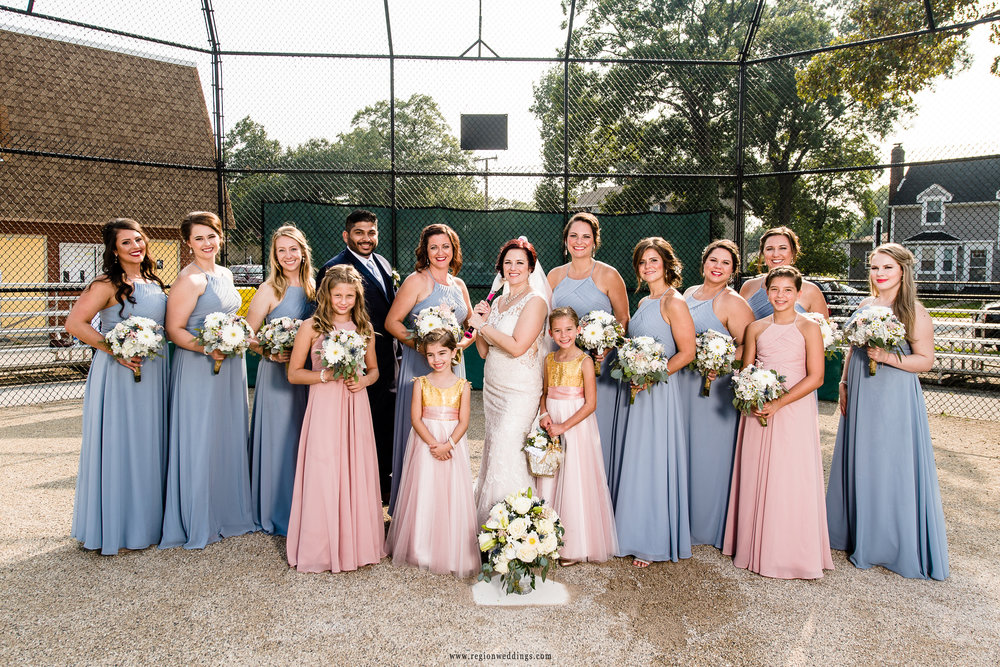 Team bride behind home plate for a baseball themed wedding photo.
