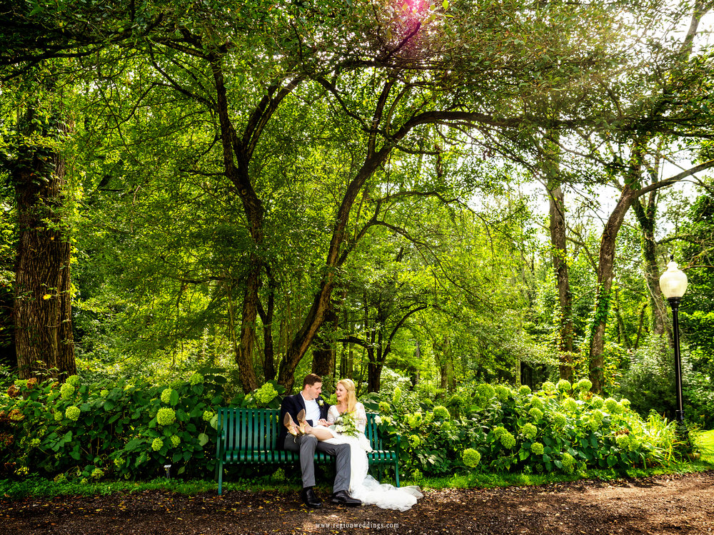 Bride and groom take a rest on a park bench at International Friendship Garden.