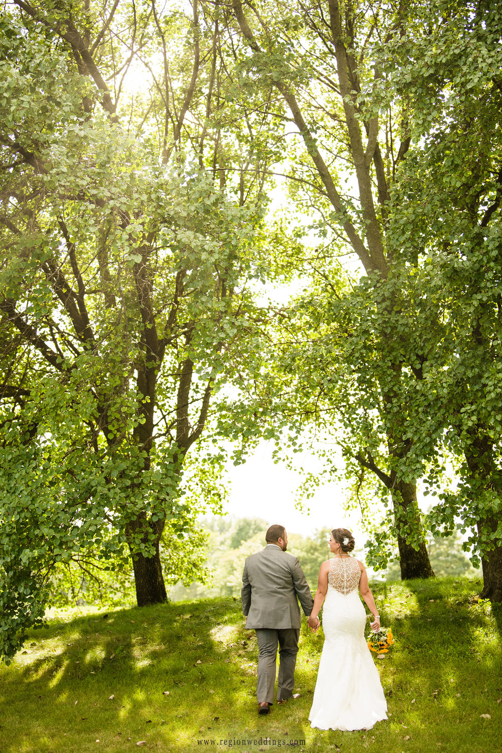 A romantic walk up a sun drenched hill for the bride and groom.