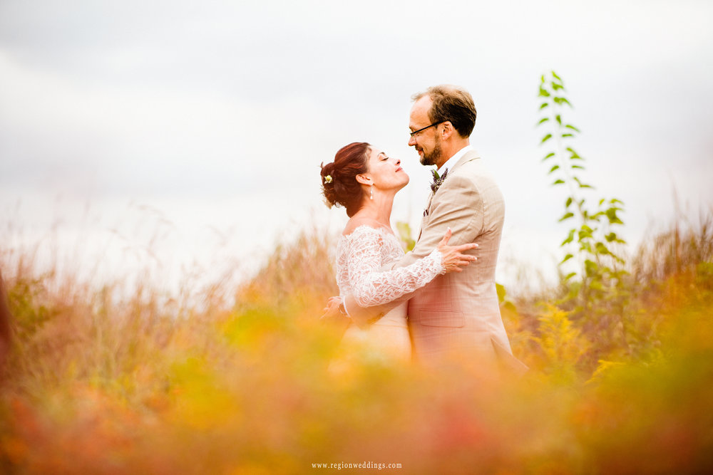 Bride and groom embrace in the Illinois fields.