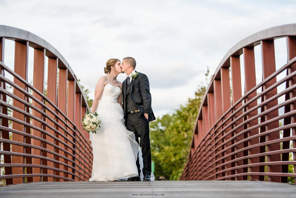 Newlyweds smooch on the Centennial Park bridge.