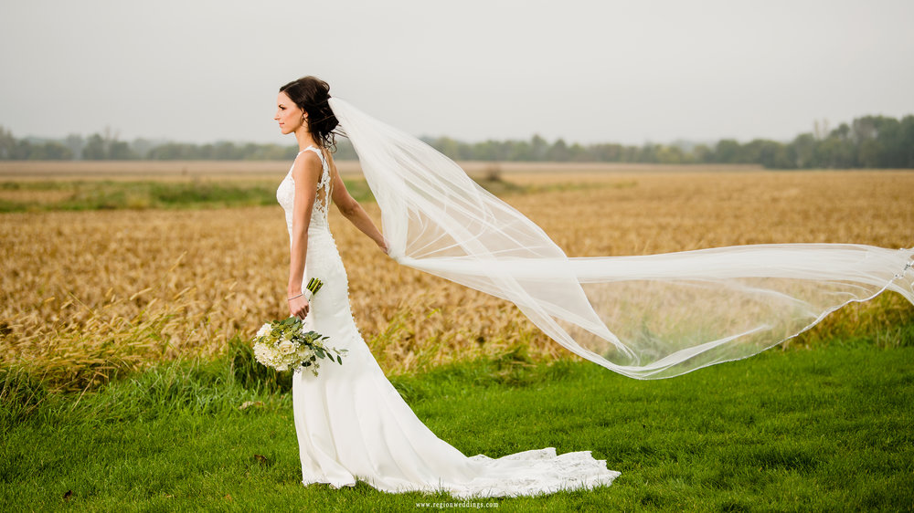 Wind blows the long veil during bridal portraits.