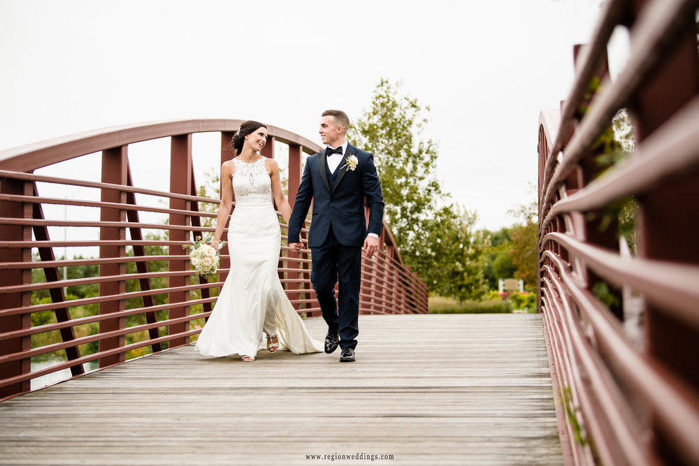 Bride and groom take a romantic walk on the bridge at Centennial Park.