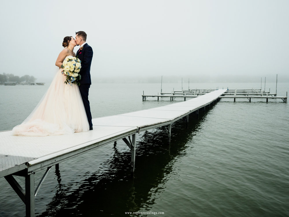 Bride and groom kiss on the Lighthouse Restaurant pier as the fog rolls in.