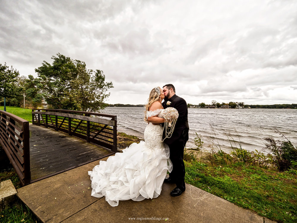 Storm clouds fill the sky as the bride and groom kiss on the edge of Pine Lake in Laporte, Indiana.
