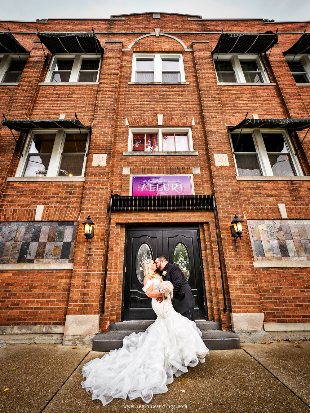 The groom dips his bride in front of The Allure wedding venue in Laporte, Indiana.