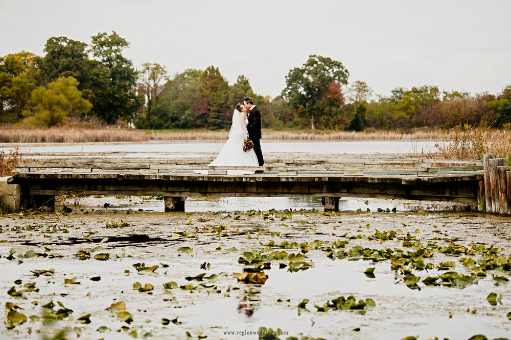 Newlyweds share a kiss on the bridge at Sand Creek Country Club.