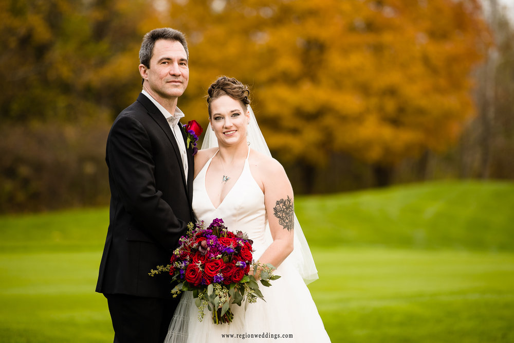 Fall color surrounds the Sand Creek golf course for bride and groom portraits.