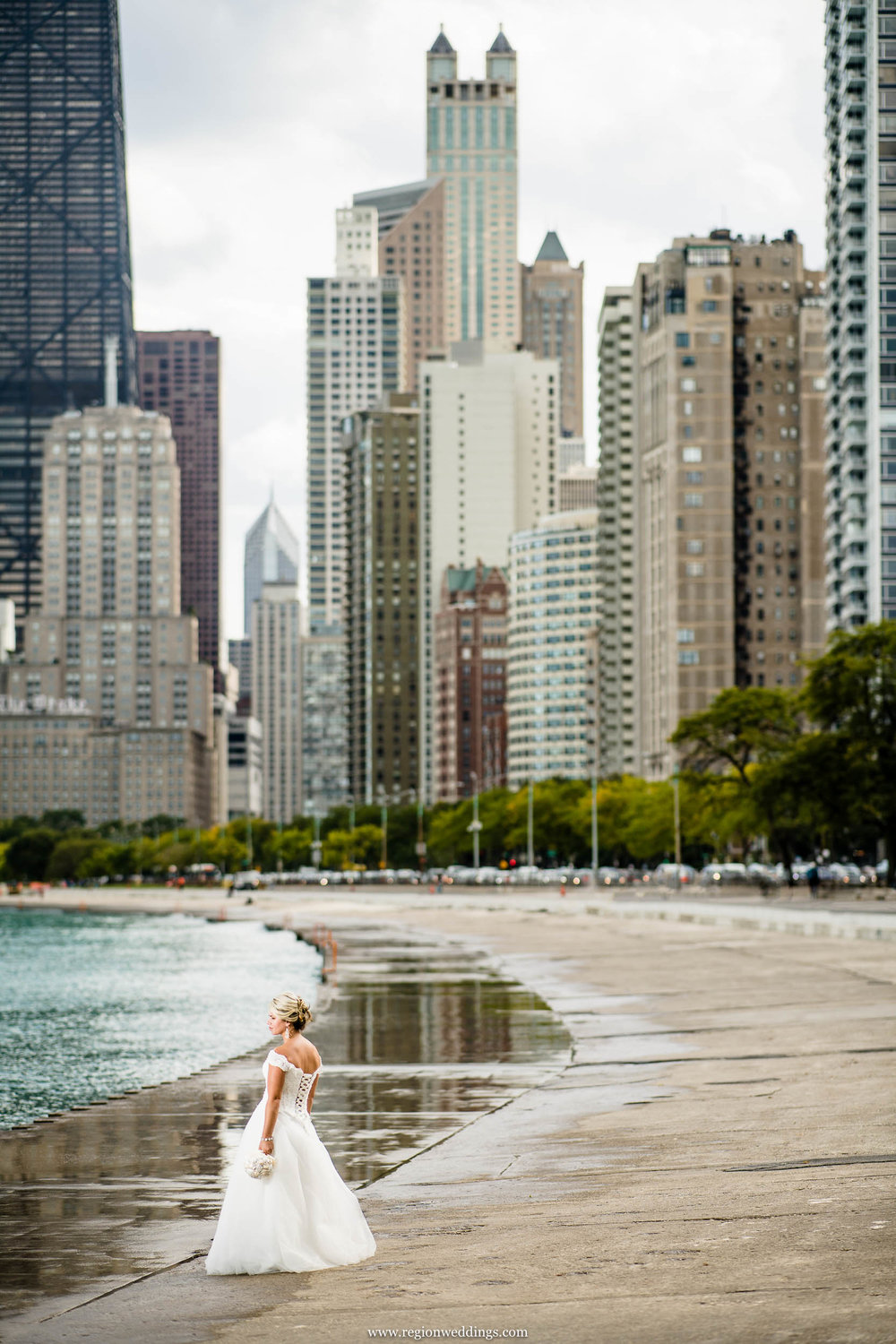 Bride alone on North Avenue Beach with Chicago skyscrapers in the background.