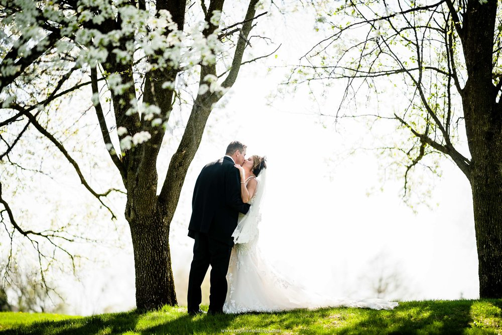 Bride and groom steal a kiss on a hilltop at Briar Ridge Golf Course.