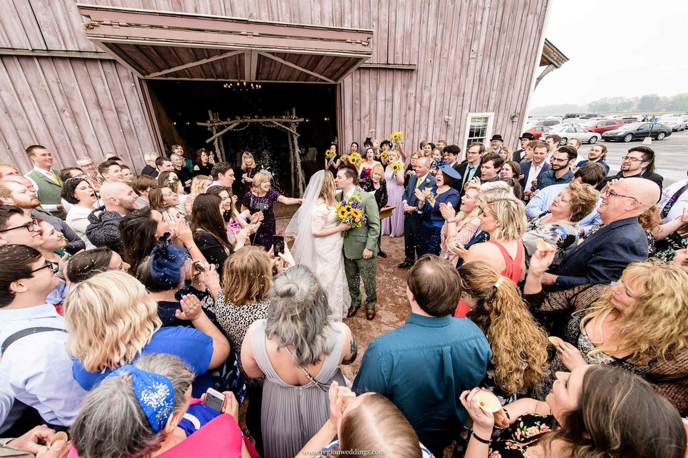 The bride and groom exit the County Line Orchard south barn after their ceremony.