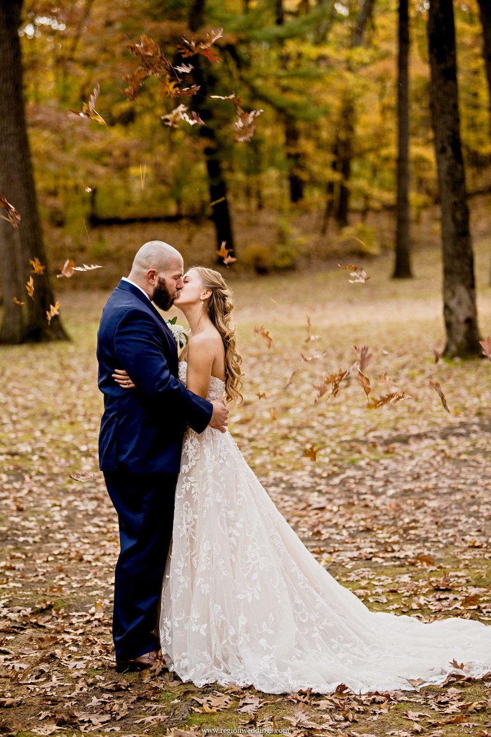 Leaves fall upon the bride and groom for their Autumn wedding.