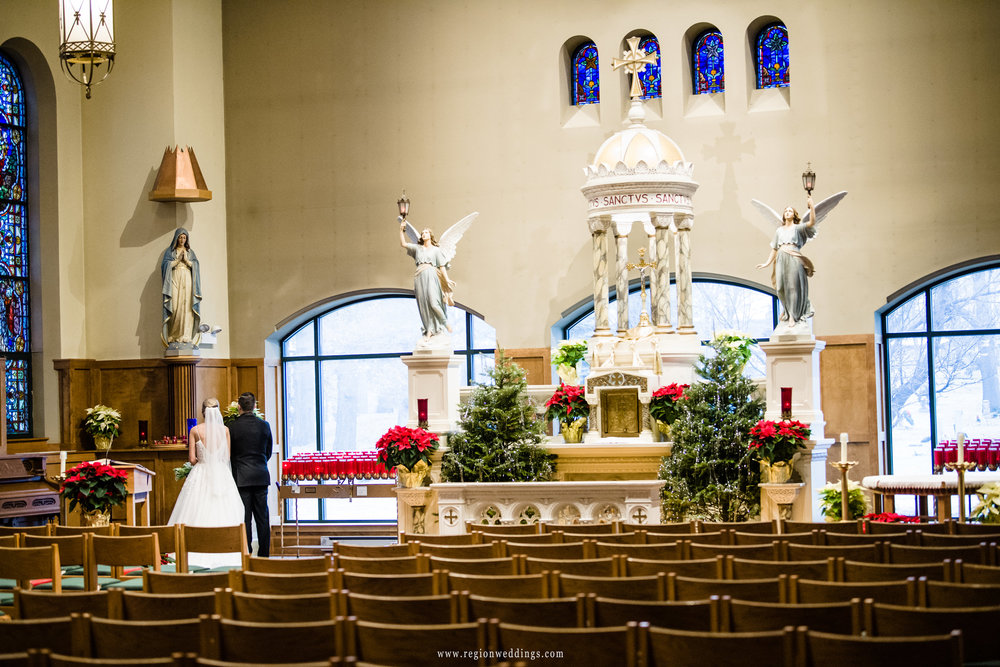 Bride and groom pray inside the sanctuary at St. Michael's Parish in Schererville, Indiana.