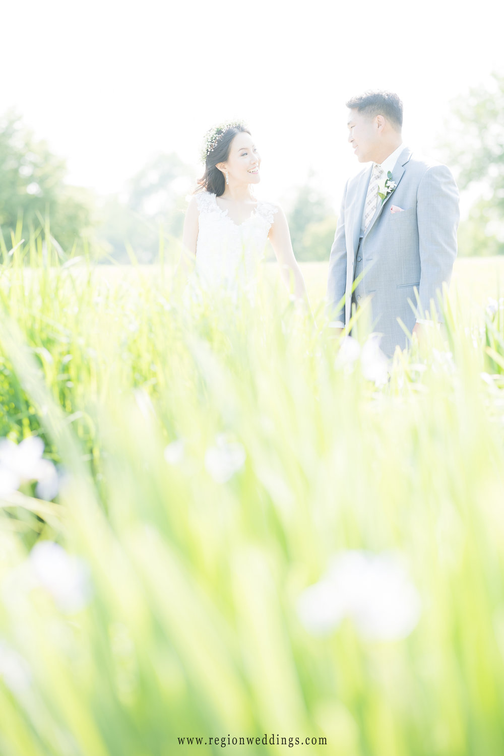 Bride and groom soak up the sun in this backlit wedding picture.
