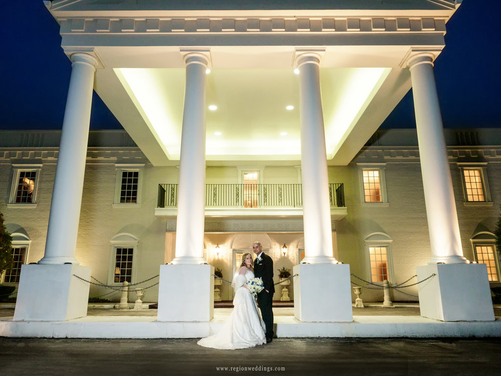 Bride and groom in front of the pillars at Chateau Bu Sché in Alsip, Illinois