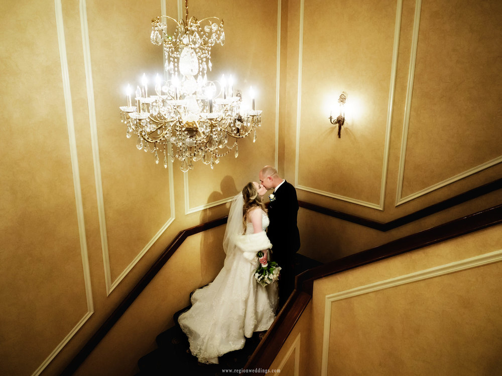 Bride and groom kiss underneath a chandelier on the staircase at Chateau Bu-Sché.