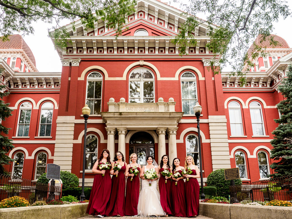Bridesmaids walk along the cobble stone entrance of the Old Crown Point Courthouse.