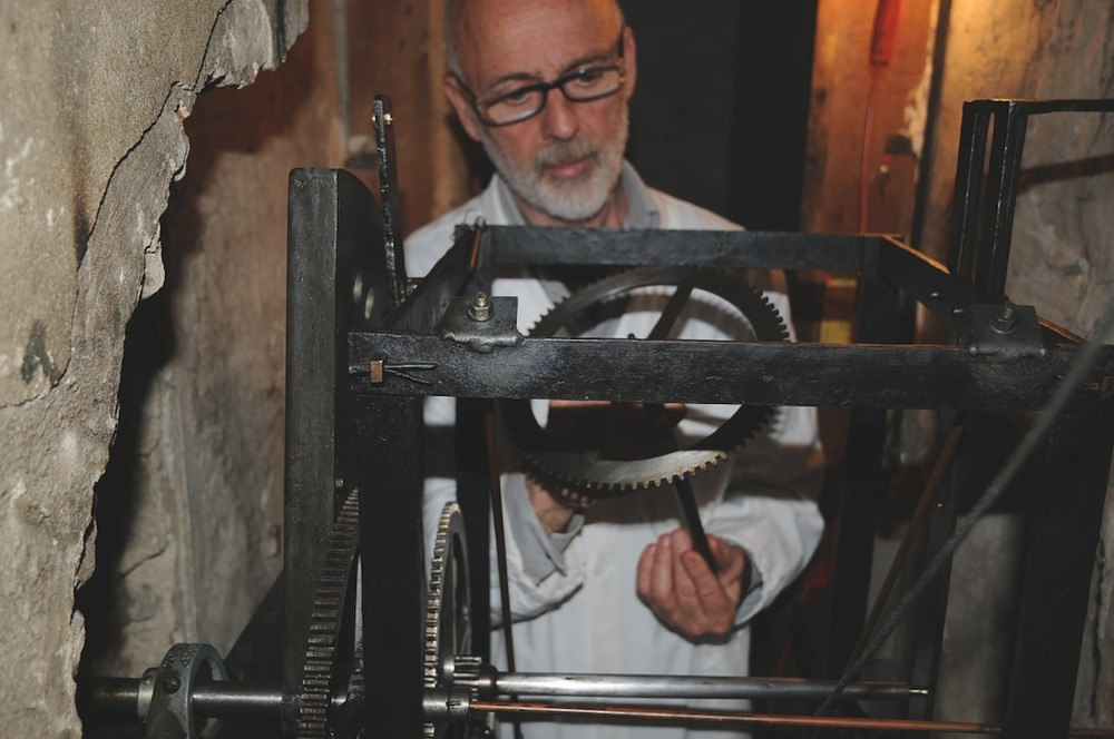 Professor Andrea Palmieri examines the gears on the clock's mechanism.