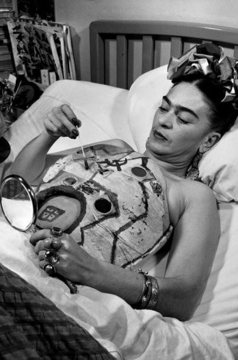 Frida Kahlo in a hospital bed, drawing on her cast with the help of a mirror, 1951.jpg