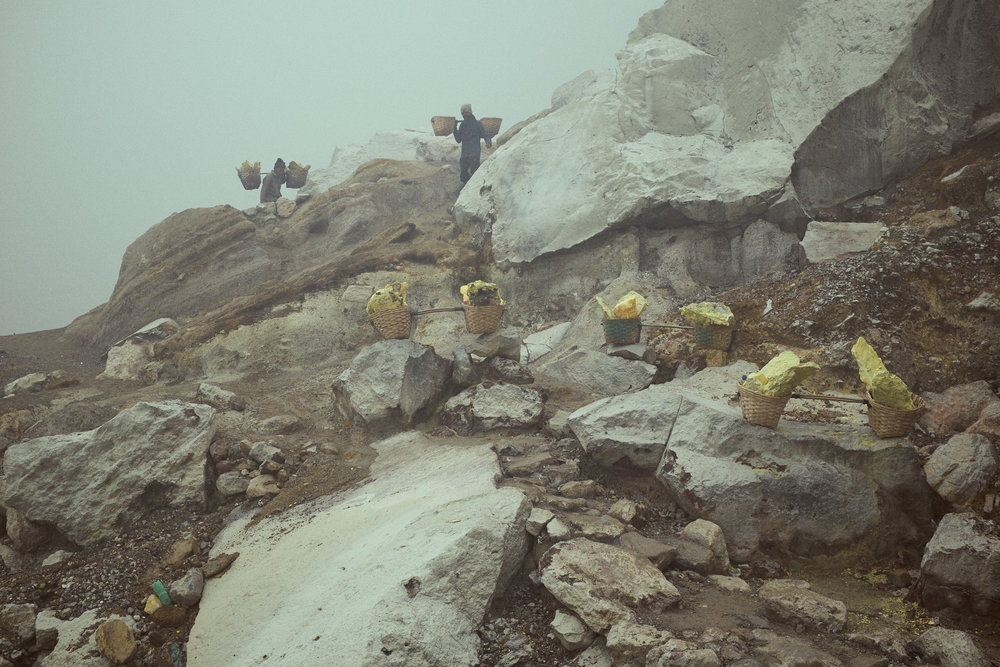 Miners work with three loads shuttling them up the crater in short distances. Paid by the kilo that they transport to the weigh station at the bottom of the mountain.  Ijen Crater, Java, Indonesia. Ijen is mined for sulphur. ©Laurence Gibson