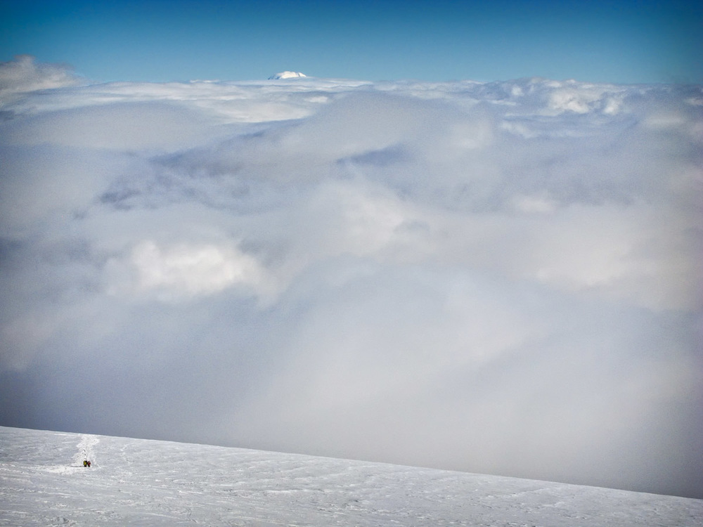 The final ascent to Camp Muir with Mt. Adams at 12,280 ft peaking above the clouds.