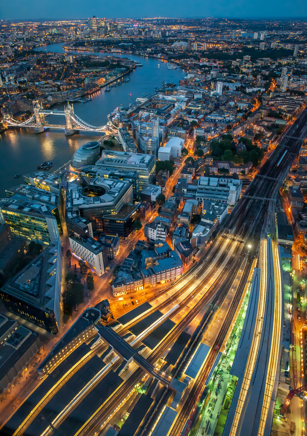 Tracks from London Bridge rail station snake out to the South East and beyond while Tower Bridge and Canary Wharf light up the skyline