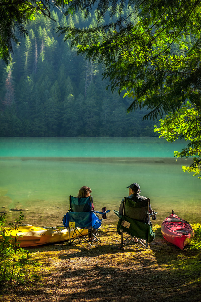 Campers enjoying morning coffee on the lake at Colonial Creek Campground in North Cascades National Park.