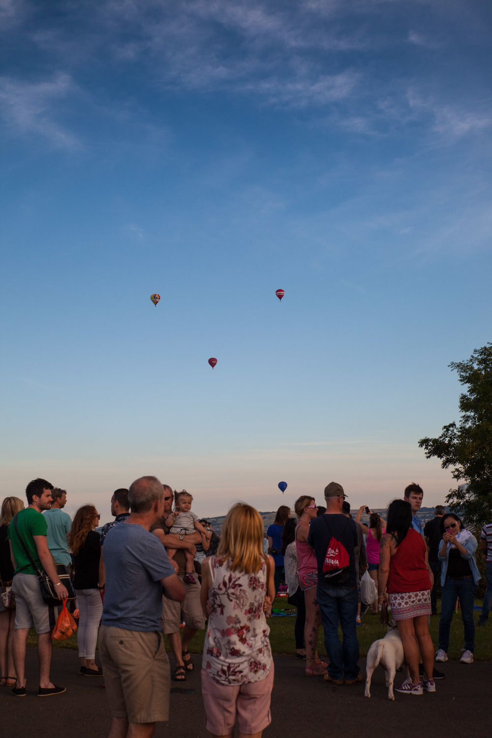 Punters enjoy the sunset on the hill as some of the balloons sail overhead.