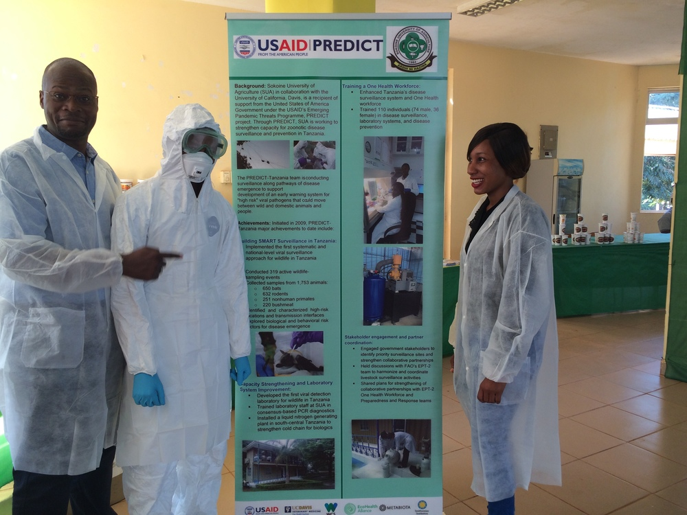 Above: Abel, Walter (in Tyvek) & Ismaralda (lab intern) standing by PREDICT banner positioned at PREDICT table.