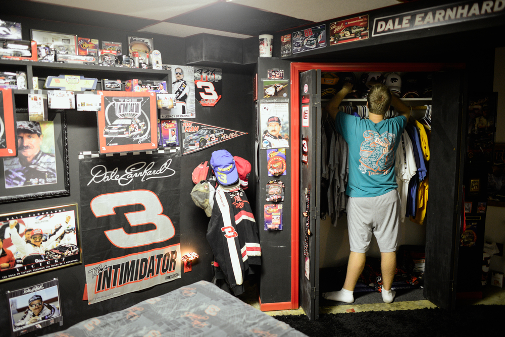 Trenton, Missouri. 2013.  Dalton straightens his hat collection in his bedroom closet. While a fan of many sports his bedroom is dedicated exclusively to Dale Earnhardt.