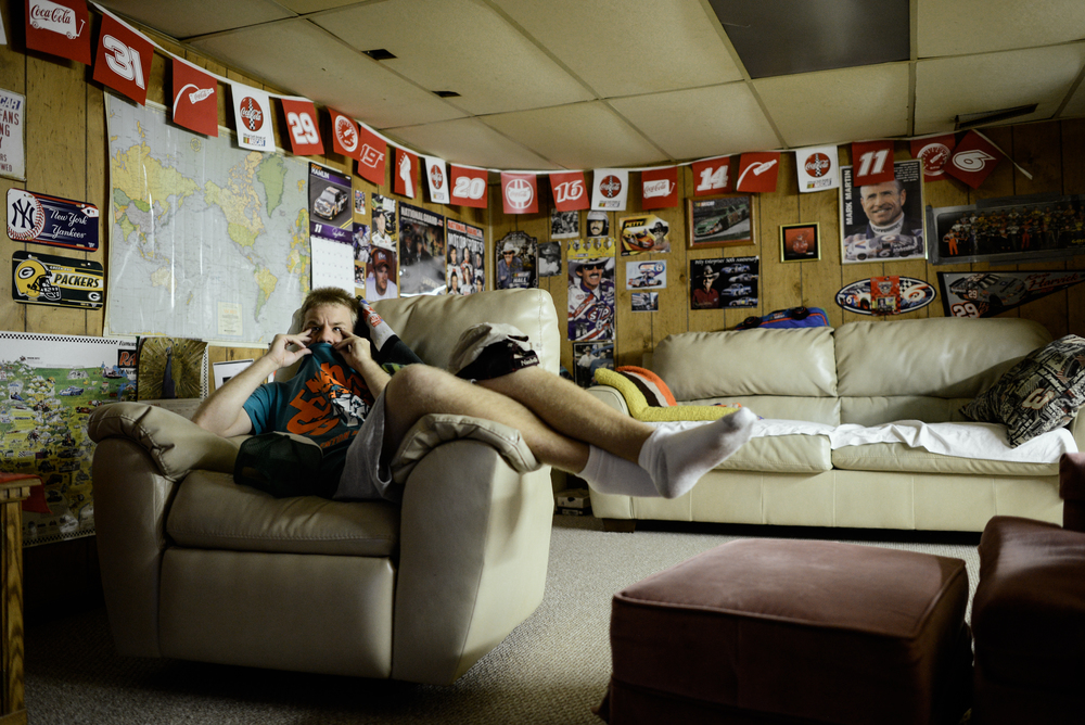 Trenton, Missouri. 2013.  Dalton watches television downstairs in his safe haven decorated with his favorite sports memorabilia. He finds comfort in sitting with his hands and shirt on his face when he watches television.