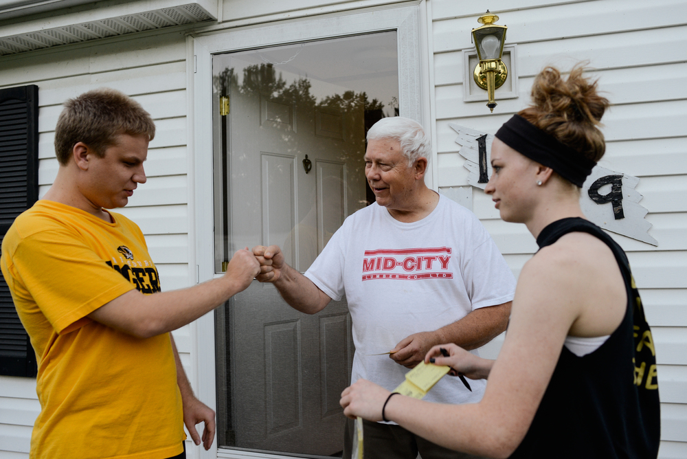 Trenton, Missouri. 2013.  A neighbor greets Dalton and his sister, Angela, as they sell raffle tickets. People in the community enjoy him stopping by.