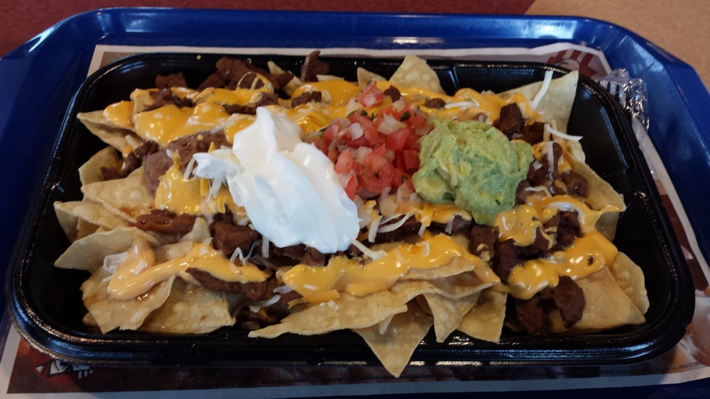 """Tortilla chips prepared fresh daily piled high with hearty beans, a three-cheese blend, warm nacho cheese sauce, guacamole, pico de gallo, reduced-fat sour cream, and steak, steak and more steak."""