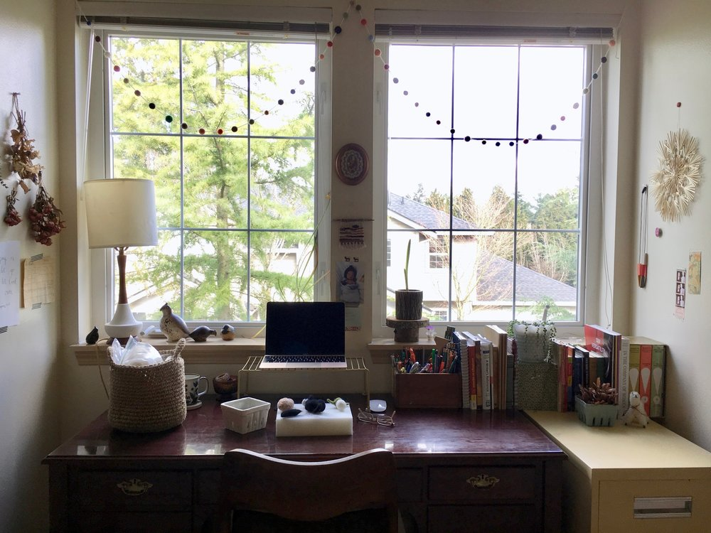 I work a lot at my desk. It serves double-duty for teaching (my other job) and running my business. I keep books as well as art supplies on top for easy access. I made the felted pom pom garland over the windows to make the space feel more fun and colorful, and the small weaving I made on our road trip moving to the Pacific Northwest from Ohio; it's inspired by North Dakota. Most other items here in this view are pieces of inspiration I have thrifted; they make me happy or inspire my work in some way.