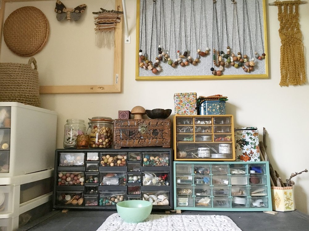 This is a closer view of where I store my beads and completed necklaces. I've taken thecork board as a display at craft fairs, and it helps to keep the necklaces here in the studio, too. I also hang my work-in-progress weavings and macrame, and felted items here.
