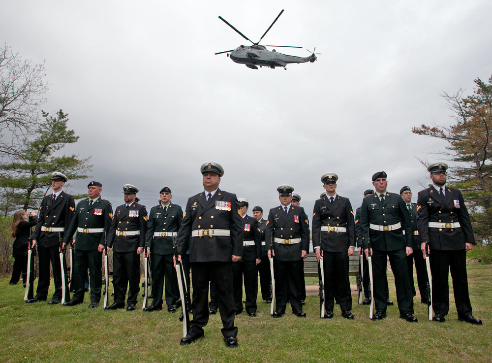 A helicopter makes a flypast of Deadman's Island over the heads of the Honour Guard during a Memorial Day ceremony.