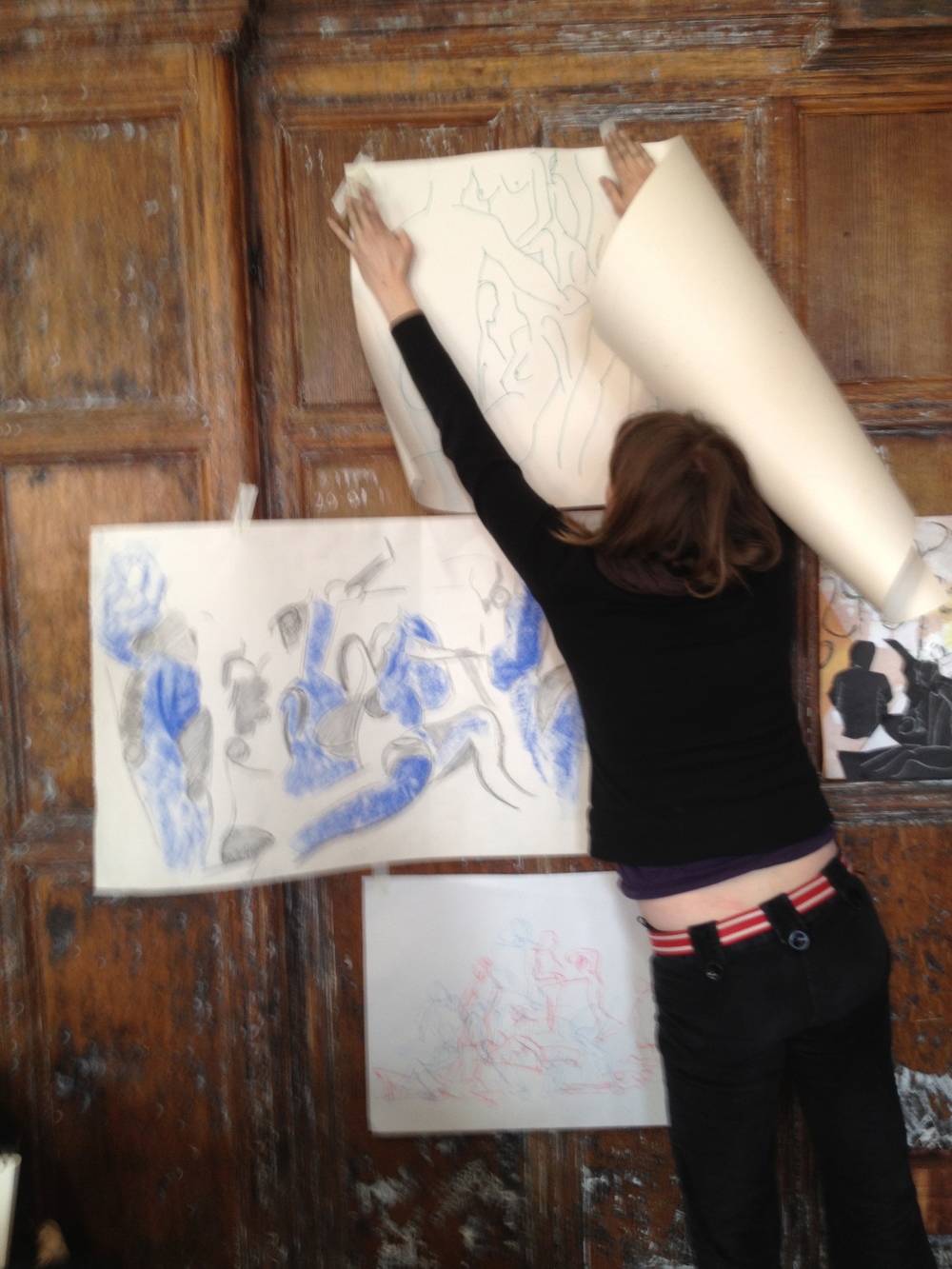 An artist attending a London Drawing event at the Battersea Arts Centre tapes one of her drawings to the wall.
