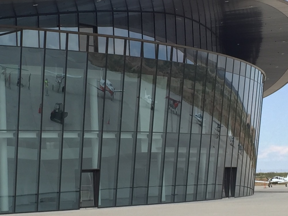 A ramp full of visiting airplanes is reflected in the terminal windows.