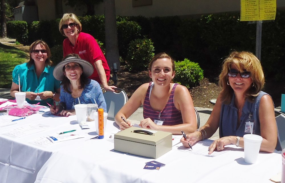 Volunteees poose at Registration Benefit table May 2014.jpg