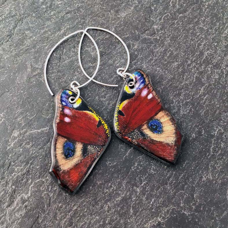 "Peacock Butterfly Earrings, Kiln Formed Art Glass, 1"" x 2.5"" x .25"", Earrings, image painted with glass enamels, clear art glass, kiln formed, Argentium sterling silver ear wires, $175.00."