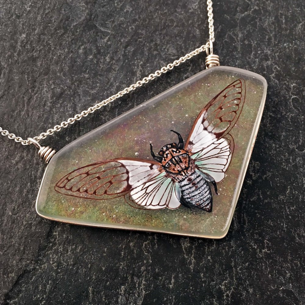 "1. White Ghost Cicada Necklace, kiln formed art glass, 2.75"" x 2"" x .25"", Necklace, image painted with glass enamels, clear art glass with a rainbow iridescent coating, kiln formed, Argentium sterling silver wire setting and chain, $325.00."