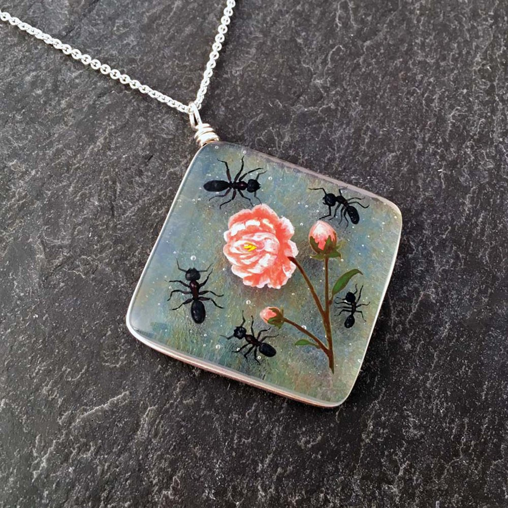 "2. Peony and Friends Necklace, kiln formed art glass, 1.75"" x 2.25"" x .25"", Necklace, image painted with glass enamels, clear art glass with a rainbow iridescent coating, kiln formed, Argentium sterling silver wire setting and chain, $175.00."