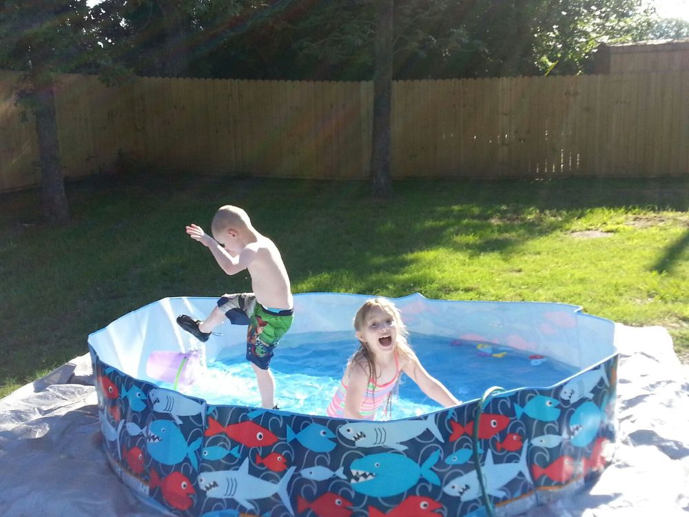 "Grace and Ezra in their ""making memories"" kiddie pool. I would love to have taken a picture of Ezra in his mud puddle for you all, but every time I got near the puddle he would pull me back down into it!"