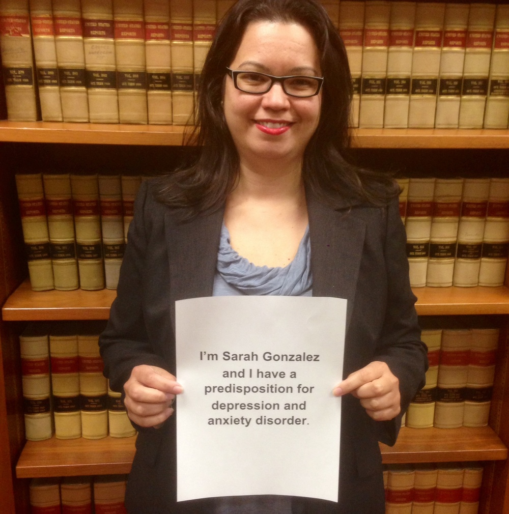"Sign: ""I'm Sarah Gonzalez and I have a predisposition for depression and anxiety disorder.""  Image description: 40 year old Latina with brown hair wearing glasses in a Judicial Chambers at a Federal Court with law books in background and holding a sign"