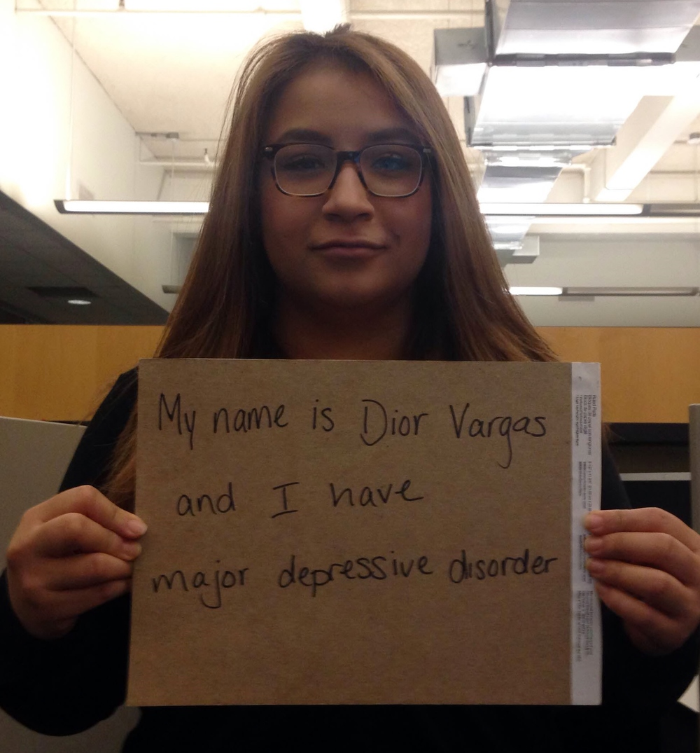 "Sign: ""My name is Dior Vargas and I have major depressive disorder""  Image description: Latina with long strawberry blonde hair wearing glasses holding a sign"