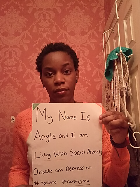"Sign: ""My name is Angie and I am living with social anxiety disorder and depression #noshame #nostigma""  Image description: African American woman with short, cropped natural hair and an orange sweater holding a sign."