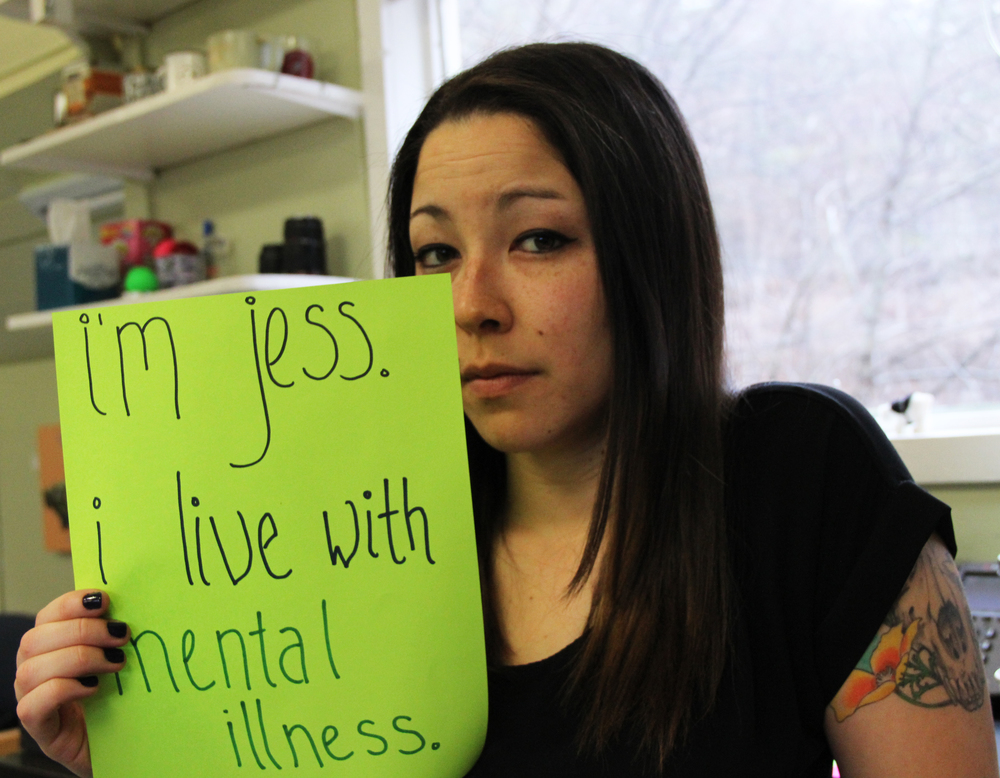 "Sign: ""I'm Jess. I live with mental illness.""  Image Description: Mixed Asian American woman with long brown hair and a black short sleeved shirt is looking forward to the camera and holding a sign."