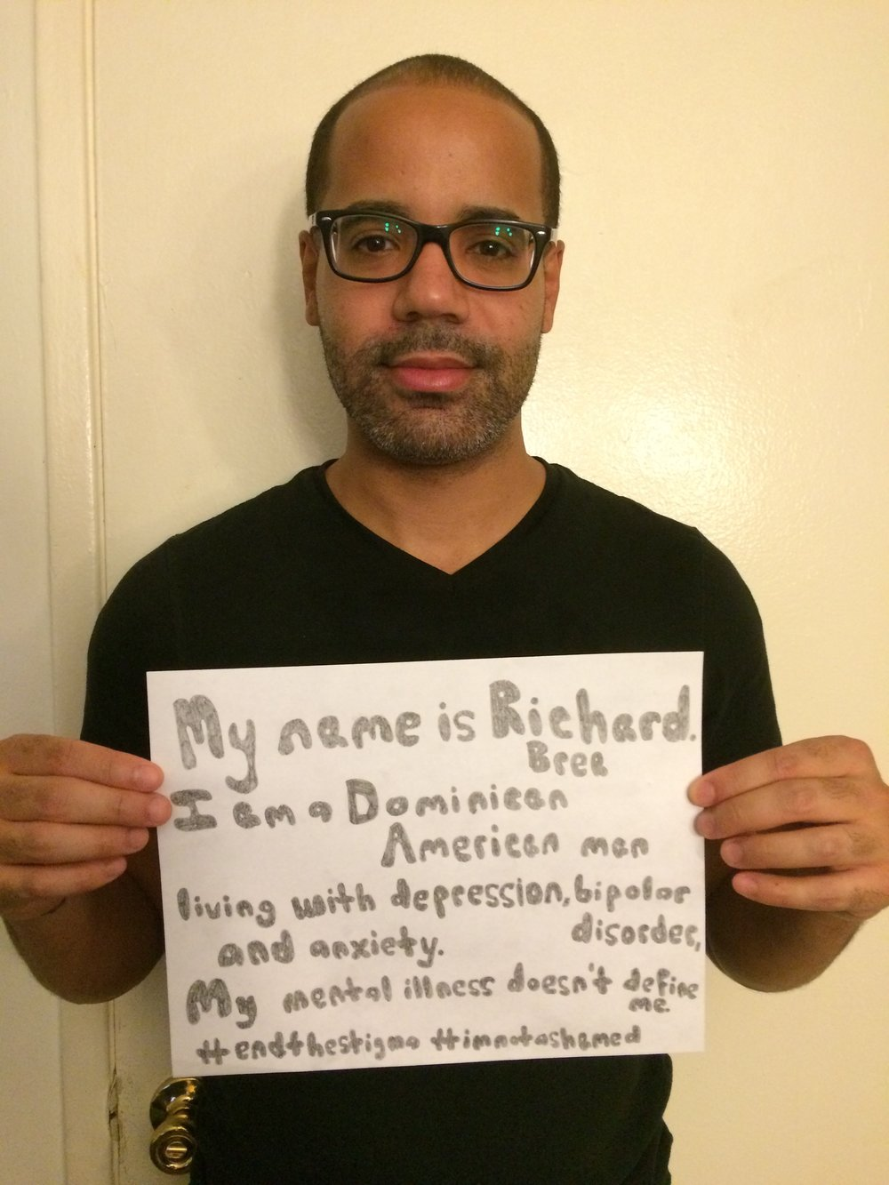 "Sign: ""My name is Richard Brea. I am a Dominican American man living with depression, bipolar disorder, and anxiety. My mental illness doesn't define me. #endthestigma #imnotashamed""  Image description: A Dominican-American man wearing glasses and a black t-shirt."