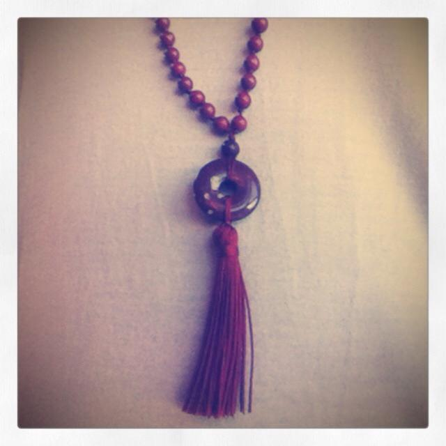 Knotted gemstone mala, with a gemstone ring above the tassel symbolizing the cyclical nature of life and spirit.